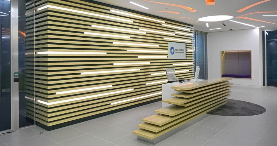 Plexwood® RBC Investor Services bank relief wall with incorporated lights and reception desk in poplar comprised surface plywood